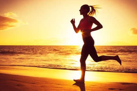 Foto de Woman running on the beach at sunset - Imagen libre de derechos