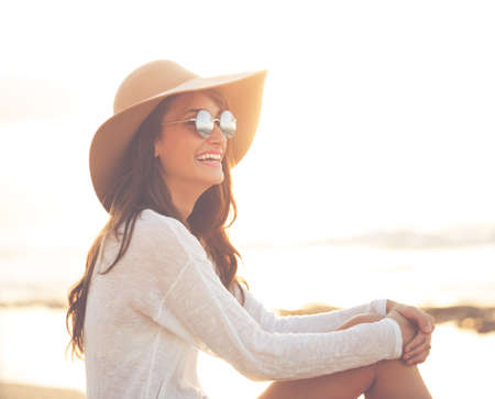 Photo pour Stylish Fashion Woman on the Beach at Sunset, Bright Warm Sunny Portrait - image libre de droit