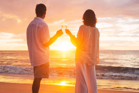 Photo for Happy Romantic Couple Enjoying Glass of Champagne at Sunset on the Beach. Vacation Travel Retirement Anniversary Celebration. - Royalty Free Image