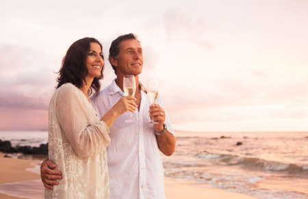 Foto de Happy Romantic Mature Couple Drinking Champagne on the Beach at Sunset. Vacation Travel Retirement Anniversary Celebration. - Imagen libre de derechos