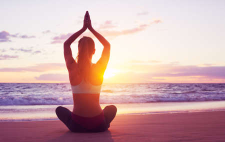 Foto de Young healthy woman practicing yoga on the beach at sunset - Imagen libre de derechos