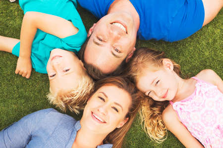 Photo pour Portrait of Happy Family of Four Outside On the Grass - image libre de droit