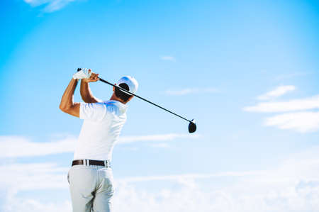 Photo for Man Swinging Golf Club with Blue Sky Background - Royalty Free Image