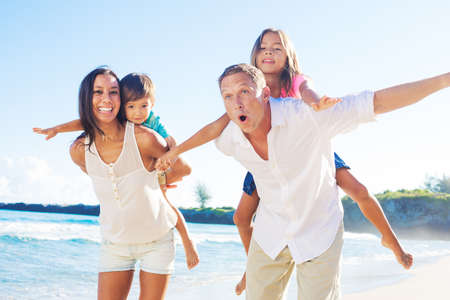 Photo pour Happy Mixed Race Family of Four Playing on the Beach - image libre de droit