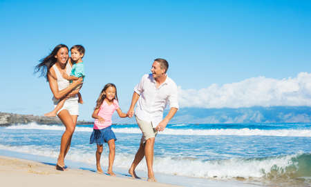 Foto de Happy Mixed Race Family of Four Playing on the Beach - Imagen libre de derechos