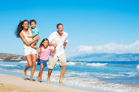 Foto de Happy Mixed Race Family of Four on the Beach - Imagen libre de derechos