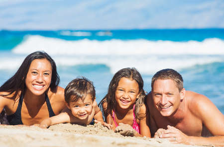 Foto de Happy Mixed Race Family of Four Playing and Having Fun on the Beach in the Sand. Tropical Beach Family Vacation. - Imagen libre de derechos