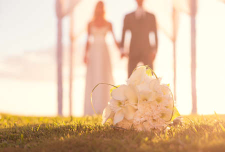 Photo pour Close up of Wedding Bouquet. Focus on Flowers. Bride and Groom in Background. - image libre de droit