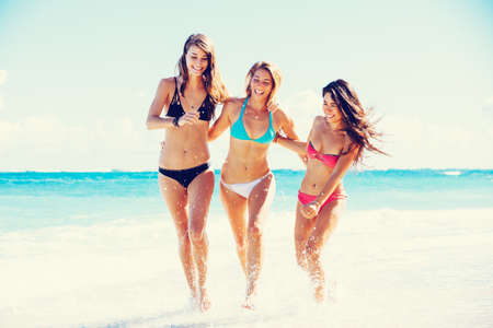 Photo pour Group of Three Beautiful Attractive Young Women Walking on the Beach - image libre de droit