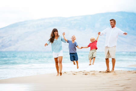 Photo for Happy Young Family Walking Down the Beach at Sunset - Royalty Free Image