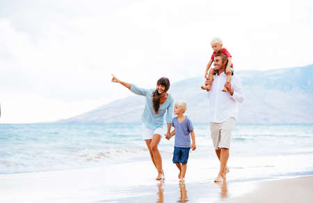 Photo pour Happy Young Family Walking Down the Beach at Sunset - image libre de droit
