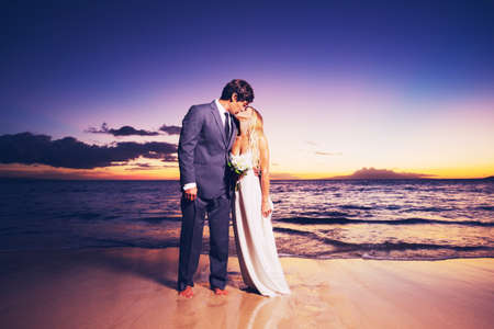 Photo pour Beautiful Wedding Couple, Bride and Groom Kissing on the Beach at Sunset - image libre de droit