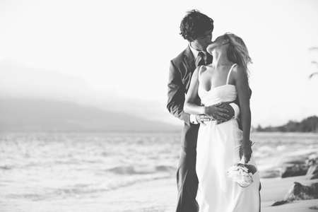 Photo pour Beautiful Wedding Couple, Bride and Groom Kissing on the Beach at Sunset. Black and White Photograph - image libre de droit