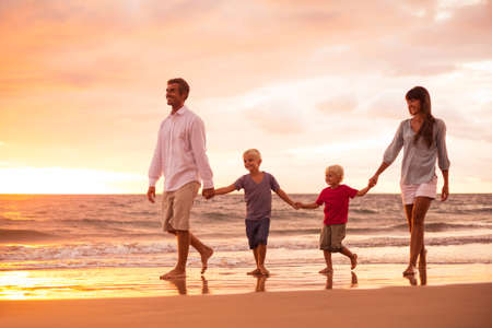 Photo pour Happy Young Family of Four on the Beach at Sunset - image libre de droit