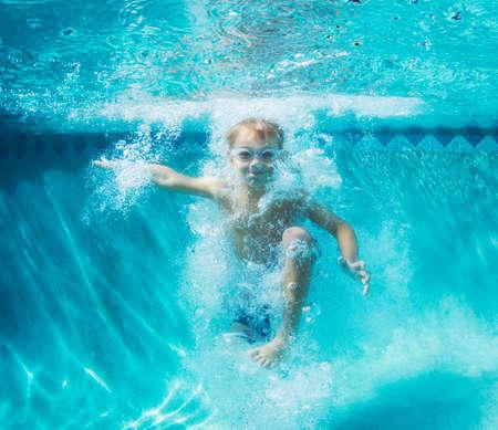 Foto de Underwater Young Boy Fun in the Swimming Pool with Goggles. Summer Vacation Fun. - Imagen libre de derechos
