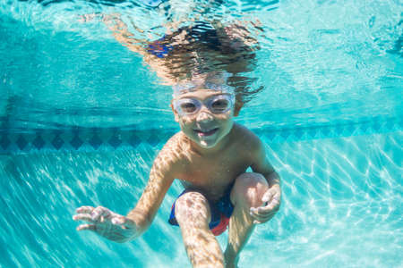 Photo pour Underwater Young Boy Fun in the Swimming Pool with Goggles. Summer Vacation Fun. - image libre de droit