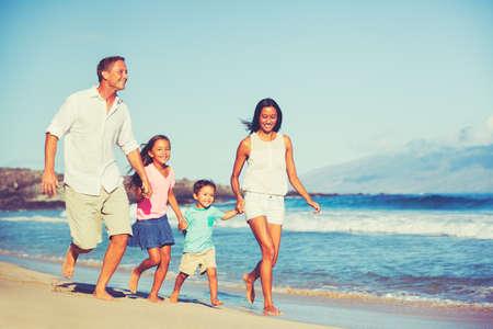 Foto de Young Happy Family Having Fun on the Beach Outdoors - Imagen libre de derechos