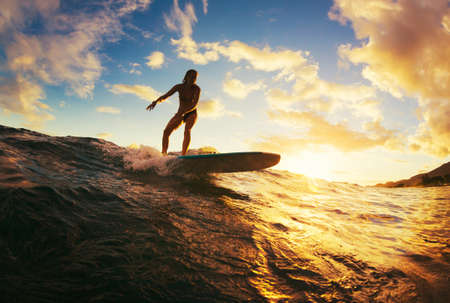 Foto de Surfing at Sunset. Beautiful Young Woman Riding Wave at Sunset. Outdoor Active Lifestyle. - Imagen libre de derechos
