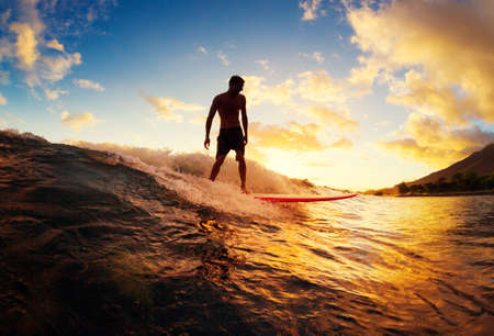 Photo pour Surfing at Sunset. Young Man Riding Wave at Sunset. Outdoor Active Lifestyle. - image libre de droit