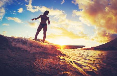 Foto de Surfing at Sunset. Beautiful Young Woman Riding Wave at Sunset. Outdoor Active Lifestyle. - Imagen libre de derechos