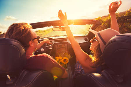 Photo pour Happy Young Couple Driving Along Country Road in Convertable at Sunset. Freedom Adevnture Roadtrip! - image libre de droit