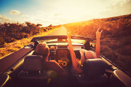 Photo for Happy Young Couple Driving Along Country Road in Convertable at Sunset. Freedom Adevnture Roadtrip! - Royalty Free Image