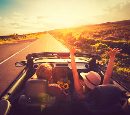 Foto de Happy Young Couple Driving Along Country Road in Convertable at Sunset. Freedom Adevnture Roadtrip! - Imagen libre de derechos