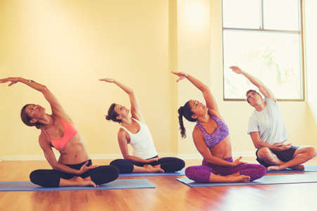 Foto de Group of People Relaxing and Doing Yoga. Wellness and Healthy Lifestyle. - Imagen libre de derechos