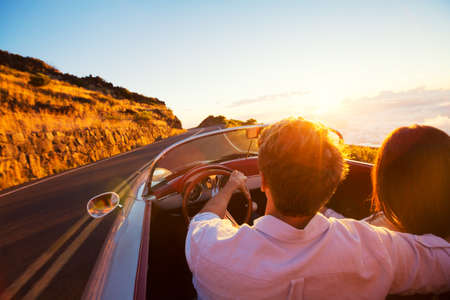 Photo pour Driving into the Sunset. Romantic Young Couple Enjoying Sunset Drive in Classic Vintage Sports Car - image libre de droit