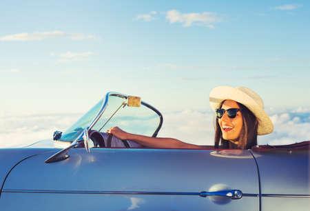 Foto de Happy Young Woman Driving in Classic Vintage Sports Car - Imagen libre de derechos