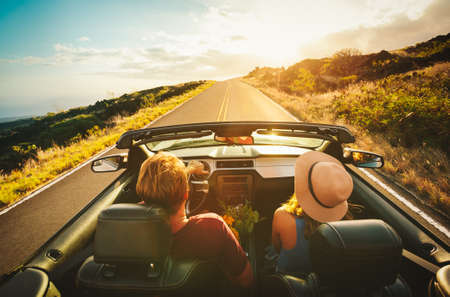 Photo for Happy Young Couple Driving Along Country Road in Convertible at Sunset - Royalty Free Image