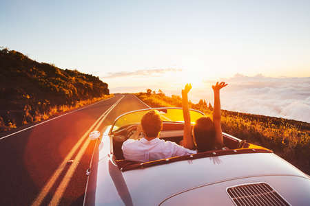 Foto de Happy Couple Driving on Country Road into the Sunset in Classic Vintage Sports Car - Imagen libre de derechos