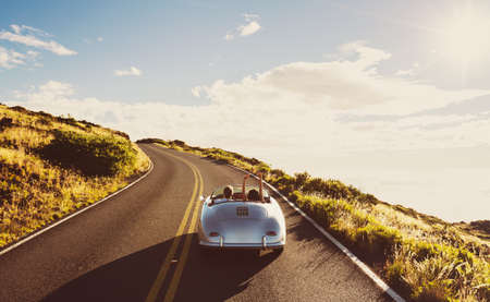 Foto de Happy Couple Driving on Country Road in Classic Vintage Sports Car - Imagen libre de derechos