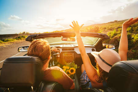 Foto de Happy Young Carefree Couple Driving Along Country Road in Convertible at Sunset - Imagen libre de derechos