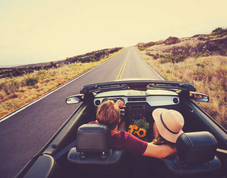 Foto de Happy Young Couple Driving Along Country Road in Convertible at Sunset - Imagen libre de derechos