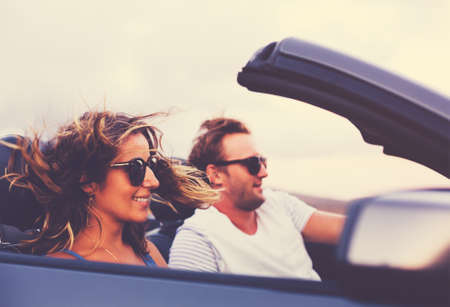 Photo pour Happy Young Couple Driving Along Country Road in Convertible at Sunset - image libre de droit