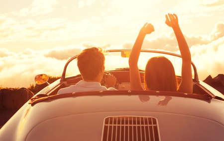 Foto de Driving into the Sunset. Happy Young Couple Enjoying the Sunset in Classic Vintage Sports Car - Imagen libre de derechos
