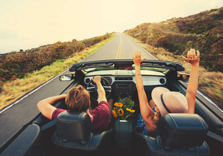 Photo pour Happy Young Carefree Couple Driving Along Country Road in Convertible at Sunset - image libre de droit