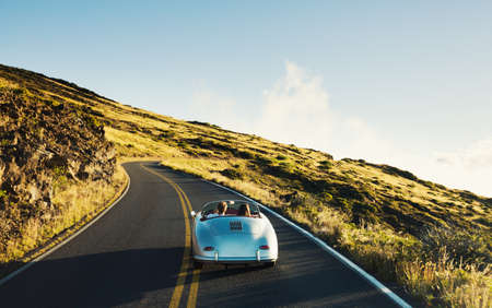 Photo pour Happy Couple Driving on Country Road in Classic Vintage Sports Car - image libre de droit