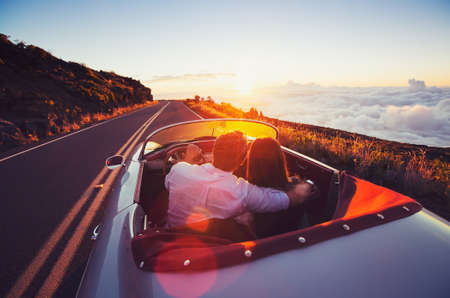 Foto per Driving into the Sunset. Romantic Young Couple Enjoying Sunset Drive in Classic Vintage Sports Car - Immagine Royalty Free