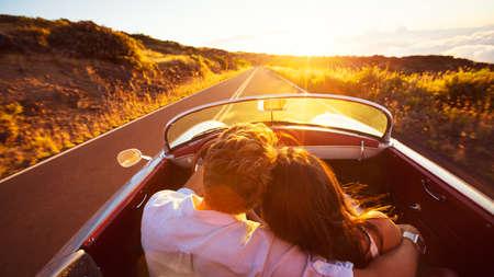 Photo pour Driving into the Sunset. Romantic Young Couple Enjoying Sunset Drive in Classic Vintage Sports Car - image libre de droit