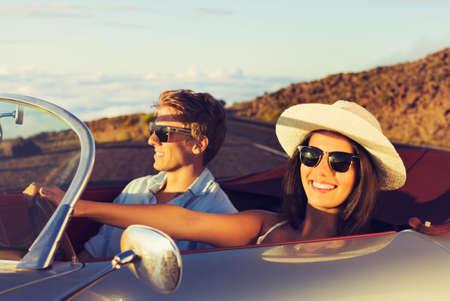 Foto de Happy Young Couple in Classic Vintage Sports Car at Sunset - Imagen libre de derechos