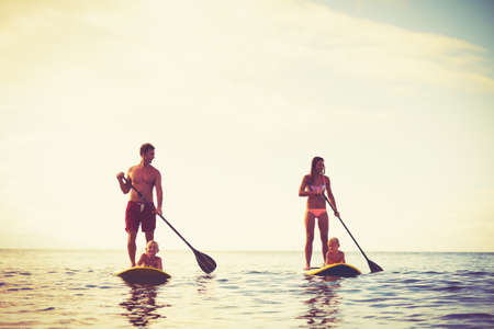 Foto de Family Having Fun Stand Up Paddling Together in the Ocean at Sunrise - Imagen libre de derechos