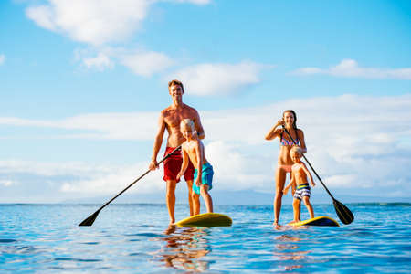 Foto de Family Having Fun Stand Up Paddling Together in the Ocean on Beautiful Sunny Morning - Imagen libre de derechos