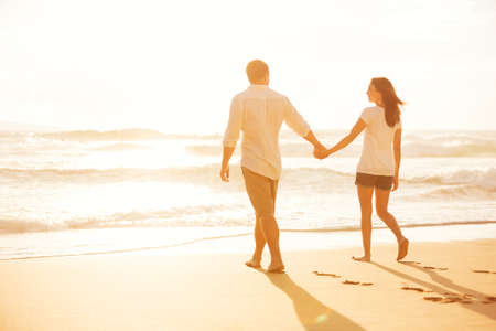 Foto de Happy Romantic Couple Walking on the Beach Enjoying the Sunset - Imagen libre de derechos