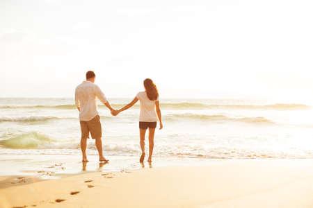 Photo pour Happy Romantic Couple Walking on the Beach Enjoying the Sunset - image libre de droit