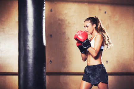 Beautiful Woman with the Red Boxing Gloves. Attractive Female Boxer Training.