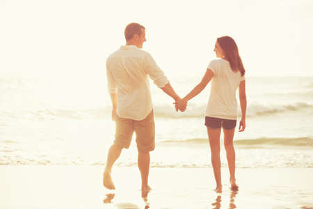 Photo for Happy Romantic Young Couple Walking Down the Beach at Sunset on Vacation - Royalty Free Image