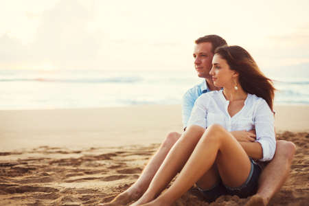 Photo pour Happy Young Romantic Couple Relaxing on the Beach Watching the Sunset. Vacation Honeymoon Getaway. - image libre de droit