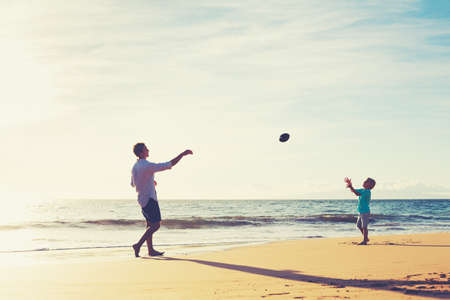 Photo for Father and Son Playing Catch Throwing Football on the Beach at Sunset - Royalty Free Image